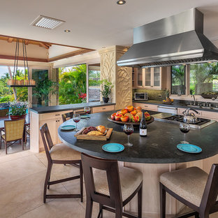 Large tropical kitchen inspiration - Inspiration for a large tropical u-shaped limestone floor kitchen remodel in Hawaii with a drop-in sink, raised-panel cabinets, light wood cabinets, concrete countertops, multicolored backsplash, stainless steel appliances and an island