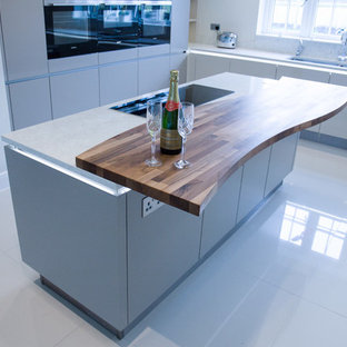 This is an example of a large contemporary u-shaped eat-in kitchen in Buckinghamshire with a drop-in sink, flat-panel cabinets, beige cabinets, quartzite benchtops, black appliances, porcelain floors and with island.