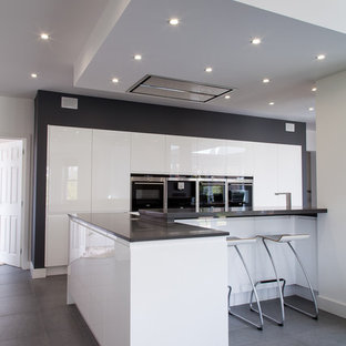 Inspiration for a medium sized contemporary kitchen/diner in Hertfordshire with flat-panel cabinets, white cabinets, engineered stone countertops, stainless steel appliances and an island.