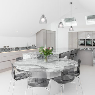 Contemporary kitchen in Cornwall with a submerged sink, flat-panel cabinets, grey cabinets, marble worktops, grey splashback, marble splashback, black appliances, an island, white floors and grey worktops.