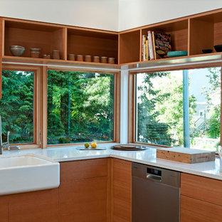 バンクーバーのコンテンポラリースタイルのおしゃれなキッチン (フラットパネル扉のキャビネット、中間色木目調キャビネット、クオーツストーンカウンター、白いキッチンパネル、シルバーの調理設備、エプロンフロントシンク) の写真