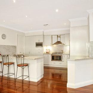 Стильный дизайн: параллельная кухня-гостиная среднего размера в современном стиле с фасадами в стиле шейкер, белыми фасадами, фартуком из мрамора, мраморной столешницей, белым фартуком, техникой из нержавеющей стали, полом из бамбука, островом, коричневым полом и белой столешницей - последний тренд