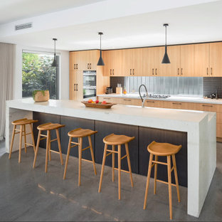 Photo of a large contemporary galley kitchen in Perth with medium wood cabinets, concrete benchtops, black splashback, window splashback, stainless steel appliances, concrete floors, with island, grey floor, white benchtop and flat-panel cabinets.