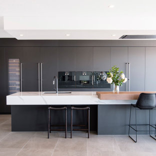 Inspiration for a contemporary galley kitchen in Brisbane with an undermount sink, flat-panel cabinets, grey cabinets, black appliances, with island, grey floor and white benchtop.