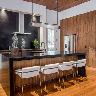 Contemporary kitchen pictures - Example of a trendy l-shaped medium tone wood floor and brown floor kitchen design in Atlanta with an undermount sink, flat-panel cabinets, medium tone wood cabinets, stainless steel appliances, an island and black countertops