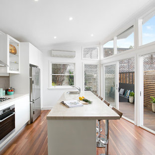 Photo of a contemporary galley kitchen in Sydney with a double-bowl sink, flat-panel cabinets, white cabinets, marble benchtops, brown splashback, stainless steel appliances, medium hardwood floors, with island, brown floor and beige benchtop.