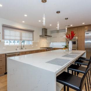 ロサンゼルスの広いコンテンポラリースタイルのおしゃれなキッチン (アンダーカウンターシンク、フラットパネル扉のキャビネット、中間色木目調キャビネット、大理石カウンター、シルバーの調理設備、淡色無垢フローリング、ベージュの床) の写真