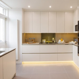Classic u-shaped kitchen in London with a submerged sink, flat-panel cabinets, white cabinets, beige splashback, stainless steel appliances, beige floors and beige worktops.