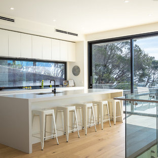 This is an example of a contemporary galley kitchen in Melbourne with an undermount sink, white cabinets, with island, window splashback, medium hardwood floors, brown floor and recessed-panel cabinets.