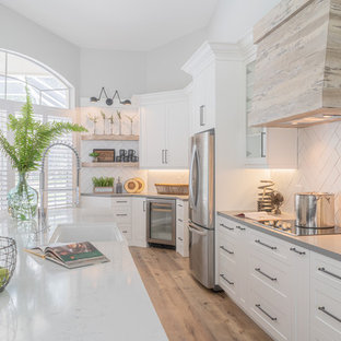Photo of a large industrial single-wall open plan kitchen in Miami with a farmhouse sink, shaker cabinets, white cabinets, quartzite benchtops, white splashback, subway tile splashback, stainless steel appliances, vinyl floors, with island, beige floor and grey benchtop.