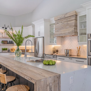 This is an example of a large country galley open plan kitchen in Miami with a farmhouse sink, shaker cabinets, white cabinets, quartzite benchtops, white splashback, subway tile splashback, stainless steel appliances, vinyl floors, with island, beige floor and grey benchtop.