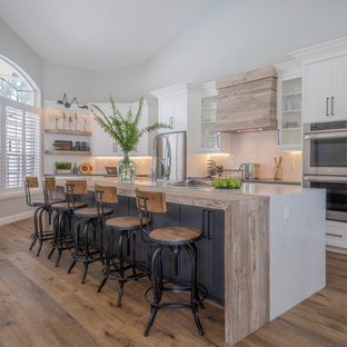 Photo of a large transitional l-shaped kitchen with an integrated sink, shaker cabinets, white cabinets, quartzite benchtops, white splashback, porcelain splashback, stainless steel appliances, vinyl floors, with island, brown floor and white benchtop.