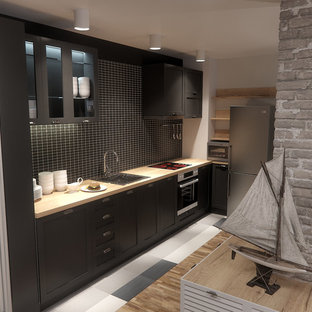 Inspiration for a mid-sized industrial l-shaped open plan kitchen in London with a drop-in sink, beaded inset cabinets, black cabinets, wood benchtops, black splashback, ceramic splashback, stainless steel appliances, terra-cotta floors and no island.