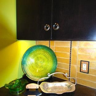 フィラデルフィアの中サイズのヴィクトリアン調のおしゃれなキッチン (アンダーカウンターシンク、フラットパネル扉のキャビネット、濃色木目調キャビネット、御影石カウンター、ベージュキッチンパネル、セラミックタイルのキッチンパネル、シルバーの調理設備の、テラコッタタイルの床) の写真