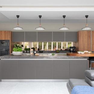 Large contemporary galley open plan kitchen in Hampshire with grey cabinets, quartz worktops, metallic splashback, mirror splashback, black appliances, an island, grey worktops, flat-panel cabinets and grey floors.