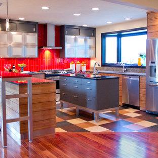 На фото: п-образная кухня в современном стиле с плоскими фасадами, техникой из нержавеющей стали, красным фартуком, фасадами цвета дерева среднего тона и красной столешницей с