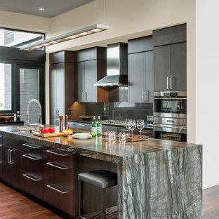 Imagen de cocina en L, actual, con fregadero bajoencimera, armarios con paneles lisos, puertas de armario de madera en tonos medios, electrodomésticos de acero inoxidable, suelo de madera oscura, una isla y suelo marrón