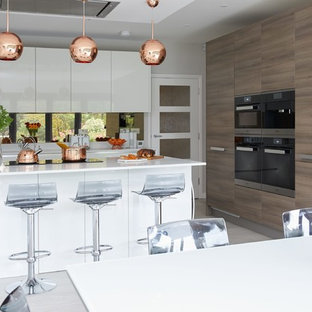 Photo of a large contemporary single-wall kitchen/diner in Hertfordshire with flat-panel cabinets, white cabinets, mirror splashback, stainless steel appliances, an island, grey floors and white worktops.