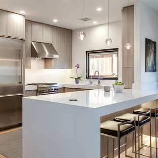 Inspiration for a mid-sized contemporary u-shaped light wood floor and brown floor open concept kitchen remodel in Denver with an undermount sink, flat-panel cabinets, gray cabinets, quartz countertops, white backsplash, stainless steel appliances and a peninsula