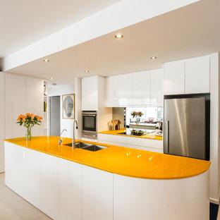 Ispirazione per una piccola cucina design con lavello sottopiano, ante lisce, ante bianche, top in quarzo composito, paraspruzzi con lastra di vetro, elettrodomestici in acciaio inossidabile e top giallo