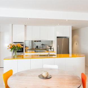Inspiration for a small contemporary galley open plan kitchen in Perth with a submerged sink, flat-panel cabinets, white cabinets, engineered stone countertops, glass sheet splashback, stainless steel appliances and yellow worktops.