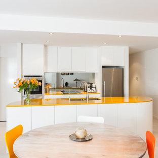 Inspiration för små moderna gult kök, med en undermonterad diskho, släta luckor, vita skåp, bänkskiva i kvarts, glaspanel som stänkskydd och rostfria vitvaror