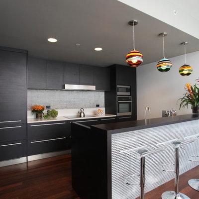 Trendy galley kitchen photo in Los Angeles with flat-panel cabinets, black cabinets, metallic backsplash, paneled appliances and metal backsplash
