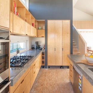 Immagine di una cucina minimal con lavello da incasso, ante lisce, ante in legno chiaro, top in cemento, elettrodomestici neri, pavimento in compensato, isola, pavimento beige e top grigio