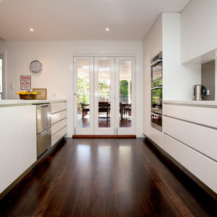 Inspiration for a large contemporary galley dark wood floor eat-in kitchen remodel in Brisbane with flat-panel cabinets, white cabinets, quartz countertops, brown backsplash, glass sheet backsplash, stainless steel appliances and an island