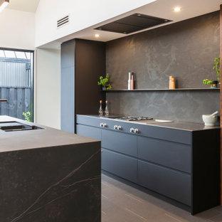 Idee per una cucina minimal di medie dimensioni con lavello sottopiano, ante lisce, ante nere, paraspruzzi nero, paraspruzzi in gres porcellanato, elettrodomestici in acciaio inossidabile, pavimento in gres porcellanato, isola e pavimento nero