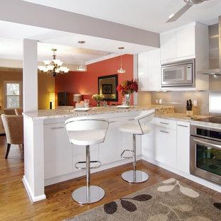 Imagen de cocina en U, contemporánea, de tamaño medio, abierta, con armarios con paneles lisos, electrodomésticos de acero inoxidable, puertas de armario blancas, encimera de granito y suelo de madera oscura