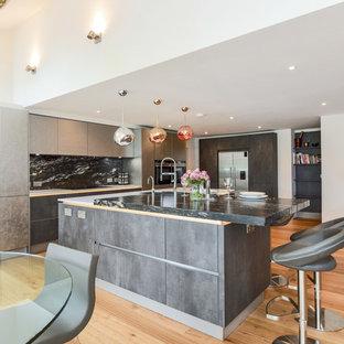 Large contemporary kitchen/diner in Berkshire with flat-panel cabinets, grey cabinets, granite worktops, black splashback, stone slab splashback, an island, stainless steel appliances and light hardwood flooring.