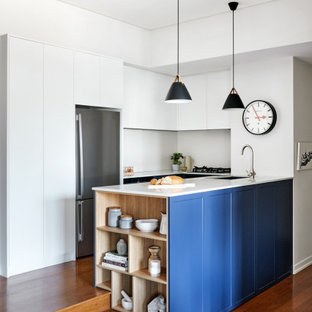 This is an example of a mid-sized contemporary u-shaped open plan kitchen in Sydney with an undermount sink, shaker cabinets, blue cabinets, quartz benchtops, white splashback, stone slab splashback, stainless steel appliances, medium hardwood floors, a peninsula, brown floor and white benchtop.