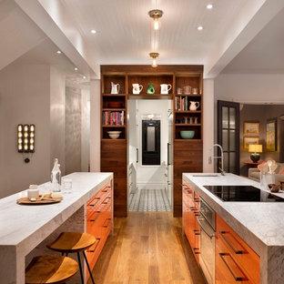 Идея дизайна: параллельная кухня-гостиная среднего размера в современном стиле с двумя и более островами, врезной раковиной, плоскими фасадами, фасадами цвета дерева среднего тона, мраморной столешницей, техникой из нержавеющей стали и паркетным полом среднего тона