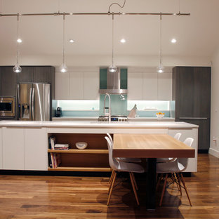 Mid-sized contemporary eat-in kitchen pictures - Example of a mid-sized trendy galley dark wood floor eat-in kitchen design in Denver with flat-panel cabinets, gray cabinets, quartz countertops, blue backsplash, glass sheet backsplash, stainless steel appliances and an island