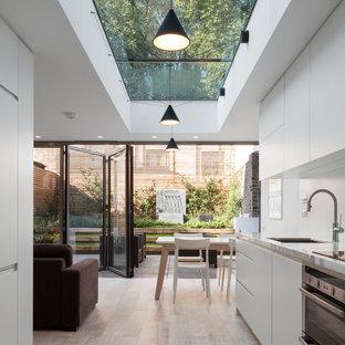 Inspiration för ett funkis kök, med en enkel diskho, släta luckor, vita skåp, bänkskiva i onyx, vitt stänkskydd, rostfria vitvaror och klinkergolv i keramik