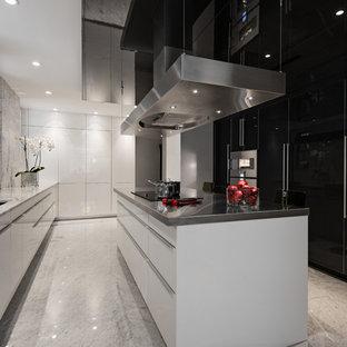 Foto di una cucina design con lavello sottopiano, ante lisce, ante bianche, top in marmo, paraspruzzi bianco, paraspruzzi in lastra di pietra e elettrodomestici in acciaio inossidabile
