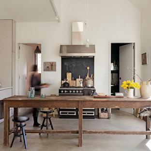 Ejemplo de cocina actual con armarios con paneles lisos, puertas de armario blancas, electrodomésticos negros y una isla