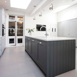 Design ideas for a large contemporary u-shaped kitchen/diner in London with a single-bowl sink, shaker cabinets, grey cabinets, granite worktops, ceramic flooring, an island, white splashback, ceramic splashback, integrated appliances, white floors and white worktops.