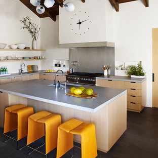 Photo of a contemporary l-shaped kitchen in San Francisco with an integrated sink, flat-panel cabinets, light wood cabinets, concrete benchtops, stainless steel appliances, with island and black floor.