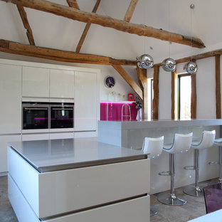 Contemporary galley kitchen in Hertfordshire with with island, flat-panel cabinets, white cabinets, pink splashback, glass sheet splashback, stainless steel appliances, grey floor and grey benchtop.