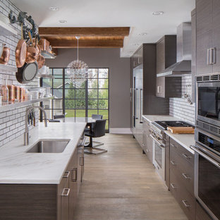 Mid-sized trendy galley eat-in kitchen photo in Other with flat-panel cabinets, brown cabinets, subway tile backsplash, stainless steel appliances, an island and an undermount sink