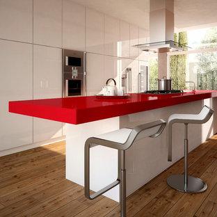Bild på ett funkis röd rött kök, med bänkskiva i kvarts