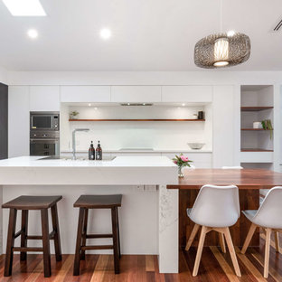 Photo of a contemporary l-shaped kitchen in Brisbane with flat-panel cabinets, dark wood cabinets, white splashback, stainless steel appliances, medium hardwood floors, with island, brown floor and white benchtop.