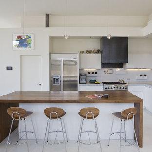 Foto di una cucina design con lavello sottopiano, ante lisce, ante bianche, paraspruzzi bianco, paraspruzzi con piastrelle di cemento, elettrodomestici in acciaio inossidabile e top in cemento