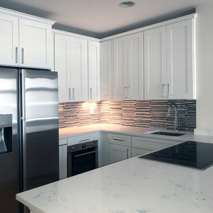 Small contemporary eat-in kitchen inspiration - Example of a small trendy u-shaped light wood floor and brown floor eat-in kitchen design in New York with a drop-in sink, shaker cabinets, white cabinets, quartz countertops, metallic backsplash, stainless steel appliances and a peninsula