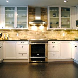 バンクーバーの中くらいのコンテンポラリースタイルのおしゃれなキッチン (ガラス扉のキャビネット、シルバーの調理設備、アンダーカウンターシンク、白いキャビネット、ベージュキッチンパネル、セラミックタイルのキッチンパネル、リノリウムの床) の写真