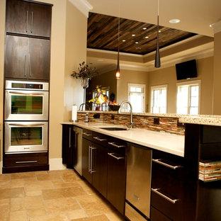 Diseño de cocina en U, actual, de tamaño medio, sin isla, con fregadero bajoencimera, armarios con paneles lisos, puertas de armario de madera en tonos medios, encimera de cemento, salpicadero marrón, electrodomésticos con paneles y suelo de terrazo
