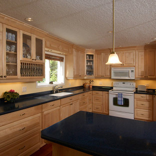 Photo of a mid-sized traditional l-shaped separate kitchen in San Diego with a double-bowl sink, raised-panel cabinets, light wood cabinets, limestone benchtops, white appliances, dark hardwood floors, with island, brown floor and black benchtop.