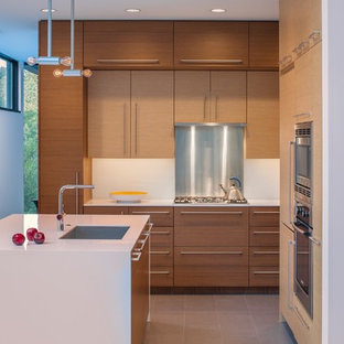 Contemporary kitchen designs - Example of a trendy u-shaped ceramic floor kitchen design in San Francisco with a single-bowl sink, flat-panel cabinets, solid surface countertops, white backsplash, an island and medium tone wood cabinets